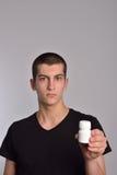 Το κιβώτιο εκμετάλλευσης νεαρών άνδρων των χαπιών στο χέρι του και παρουσιάζει τα φάρμακα Στοκ Εικόνες