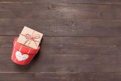 Το κιβώτιο δώρων και το δοχείο λουλουδιών είναι στο ξύλινο υπόβαθρο με κενό Στοκ φωτογραφία με δικαίωμα ελεύθερης χρήσης