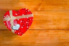 Το κιβώτιο δώρων με τη μορφή καρδιών με την επιγραφή ι σας αγαπά στο ξύλινο υπόβαθρο στοκ φωτογραφίες