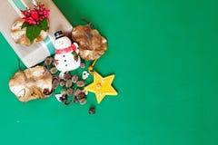 Το κιβώτιο δώρων με το κόκκινο λουλούδι, χιονάνθρωπος, κώνοι πεύκων, ξεραίνει τα φύλλα και τη διακόσμηση αστεριών στο πράσινο υπό Στοκ Εικόνες