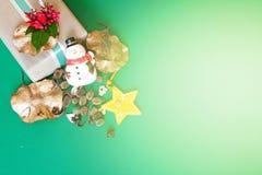 Το κιβώτιο δώρων με το κόκκινο λουλούδι, χιονάνθρωπος, κώνοι πεύκων, ξεραίνει τα φύλλα και τη διακόσμηση αστεριών στο πράσινο υπό Στοκ εικόνες με δικαίωμα ελεύθερης χρήσης