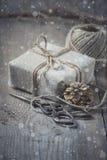 Το κιβώτιο δώρων τύλιξε το ύφασμα λινού και διακόσμησε με το σκοινί, γιούτα, διακόσμηση Χριστουγέννων Συρμένες χιονοπτώσεις Στοκ Φωτογραφίες