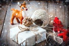 Το κιβώτιο δώρων τύλιξε το ύφασμα λινού και διακόσμησε με το σκοινί, γιούτα, διακόσμηση Χριστουγέννων Συρμένες χιονοπτώσεις Στοκ Εικόνες