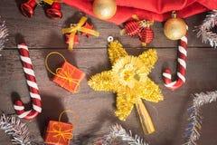 Το κιβώτιο δώρων Χριστουγέννων, το ντεκόρ τροφίμων και το δέντρο έλατου διακλαδίζονται στον ξύλινο πίνακα Στοκ Φωτογραφία