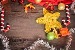 Το κιβώτιο δώρων Χριστουγέννων, το ντεκόρ τροφίμων και το δέντρο έλατου διακλαδίζονται στον ξύλινο πίνακα Στοκ Εικόνες