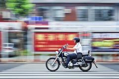 Το κινεζικό άτομο στη μοτοσικλέτα Suzuki περνά τον πίνακα διαφημίσεων, Yantai, Κίνα στοκ φωτογραφία με δικαίωμα ελεύθερης χρήσης
