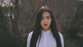 Το κινεζικό κορίτσι που εξετάζει σοβαρά τη κάμερα και ισιώνει την τρίχ φιλμ μικρού μήκους