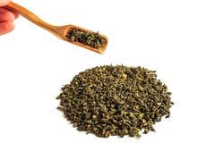 Το κινεζικό πράσινο τσάι teguanin, που διασκορπίστηκε σε ένα άσπρο υπόβαθρο, έχυσε με spatula τσαγιού και ένα φίλτρο τσαγιού στοκ εικόνες