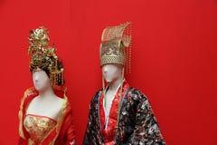 Το κινεζικό φόρεμα παράδοσης του αρσενικού και του θηλυκού ντύνεται στο μανεκέν με το κόκκινο υπόβαθρο στοκ εικόνες