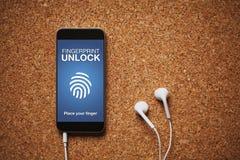 Το κινητό τηλέφωνο με το δακτυλικό αποτύπωμα ξεκλειδώνει το σύστημα στην οθόνη, τα άσπρα ακουστικά, και το διάστημα αντιγράφων Στοκ εικόνες με δικαίωμα ελεύθερης χρήσης