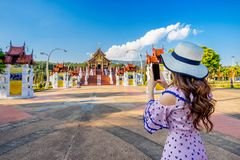 Το κινητό τηλέφωνο χρήσης γυναικών παίρνει μια φωτογραφία στο βόρειο ταϊλανδικό ύφος Ho kham luang στη βασιλική χλωρίδα ratchaphr στοκ φωτογραφίες