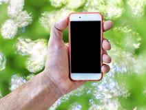 Το κινητό τηλέφωνο οθόνης αφής εκμετάλλευσης χεριών απομόνωσε το πράσινο μουτζουρωμένο υπόβαθρο Στοκ φωτογραφίες με δικαίωμα ελεύθερης χρήσης