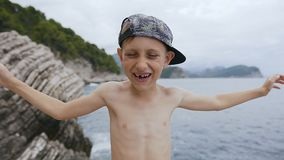 Το κλείσιμο μικρών παιδιών και ανακαλύπτει τα μάτια του με τα χέρια του Πορτρέτο ενός ευτυχούς παιδιού στην ΚΑΠ στο υπόβαθρο θάλα απόθεμα βίντεο