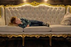 Το κοκκινομάλλες αγόρι βρίσκεται στον καναπέ Στοκ φωτογραφίες με δικαίωμα ελεύθερης χρήσης