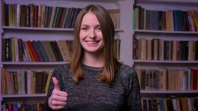 Το κοκκινομάλλες καυκάσιο κορίτσι στα ρολόγια στηριγμάτων smilingly στη κάμερα, έβαλε το δάχτυλό της μέχρι την επίδειξη όπως και  απόθεμα βίντεο