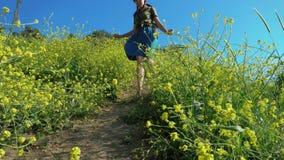 Το κοκκινομάλλες κορίτσι σε ένα καπέλο κάουμποϋ και ένα σακίδιο πλάτης περπατά σε μια πορεία βουνών φιλμ μικρού μήκους