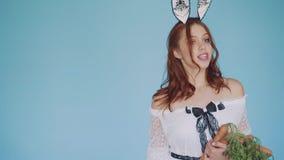 Το κοκκινομάλλες κορίτσι στην εικόνα ένα κουνέλι με τις θετικές συγκινήσεις αγκαλιάζει τα καρότα φιλμ μικρού μήκους