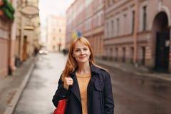Το κοκκινομάλλες κορίτσι στο ύφος των περιστασιακών περιπάτων στην πόλη επάνω Στοκ Εικόνες