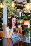 Το κοκτέιλ καφέδων κοριτσιών φρέσκο πίνει το πορτοκαλί brunette φύλλων θερινής διάθεσης ημέρας του ST Πάτρικ άσπρο ένα ριγωτό εσω Στοκ φωτογραφία με δικαίωμα ελεύθερης χρήσης