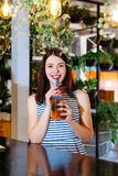 Το κοκτέιλ καφέδων κοριτσιών φρέσκο πίνει το πορτοκαλί brunette φύλλων θερινής διάθεσης ημέρας του ST Πάτρικ άσπρο ένα ριγωτό εσω Στοκ εικόνα με δικαίωμα ελεύθερης χρήσης