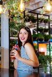 Το κοκτέιλ καφέδων κοριτσιών φρέσκο πίνει το πορτοκαλί brunette φύλλων θερινής διάθεσης ημέρας του ST Πάτρικ άσπρο ένα ριγωτό εσω Στοκ Φωτογραφία