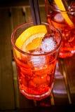 Το κοκτέιλ aperol απεριτίφ Spritz με τις πορτοκαλιές φέτες και οι κύβοι πάγου στο disco χρώματος ανάβουν το υπόβαθρο Στοκ Φωτογραφία