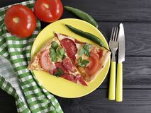 Το κομμάτι πιτσών με το μαχαίρι ιταλικά δικράνων λουκάνικων τρώει σε ένα μαύρο woodeneat Στοκ εικόνα με δικαίωμα ελεύθερης χρήσης