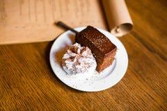 Το κομμάτι της σκοτεινής πίτας που καλύπτεται με τη μαύρη σοκολάτα που βρίσκεται κοντά στη φρέσκια κρέμα που διακοσμείται με τη σ Στοκ φωτογραφία με δικαίωμα ελεύθερης χρήσης