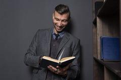Το κομψό άτομο διαβάζει το βιβλίο και χαμογελά Όμορφο άτομο στο κοστούμι με το αστείο βιβλίο στοκ φωτογραφία με δικαίωμα ελεύθερης χρήσης