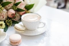 Το κομψό γλυκό επιδόρπιο macarons, το φλιτζάνι του καφέ και η κρητιδογραφία χρωμάτισαν την μπεζ ανθοδέσμη λουλουδιών στο άσπρο μά στοκ φωτογραφίες