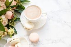 Το κομψό γλυκό επιδόρπιο macarons, το φλιτζάνι του καφέ και η κρητιδογραφία χρωμάτισαν την μπεζ ανθοδέσμη λουλουδιών στο άσπρο μά στοκ εικόνες με δικαίωμα ελεύθερης χρήσης