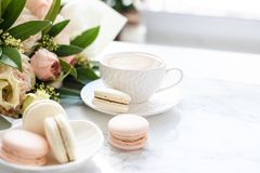 Το κομψό γλυκό επιδόρπιο macarons, το φλιτζάνι του καφέ και η κρητιδογραφία χρωμάτισαν την μπεζ ανθοδέσμη λουλουδιών στο άσπρο μά στοκ εικόνες