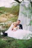 Το κομψό νέο ευτυχές γαμήλιο ζεύγος κάθεται στην πράσινη χλόη επάνω στοκ εικόνες