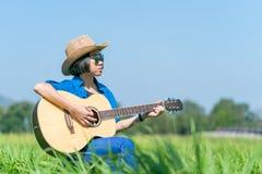 Το κοντά καπέλο και τα γυαλιά ηλίου ένδυσης τρίχας γυναικών κάθονται την κιθάρα παιχνιδιού στο γ Στοκ Εικόνες