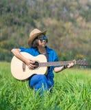 Το κοντά καπέλο και τα γυαλιά ηλίου ένδυσης τρίχας γυναικών κάθονται την κιθάρα παιχνιδιού στο γ Στοκ Εικόνα