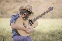 Το κοντά καπέλο και τα γυαλιά ηλίου ένδυσης τρίχας γυναικών κάθονται την κιθάρα παιχνιδιού στο γ Στοκ εικόνα με δικαίωμα ελεύθερης χρήσης