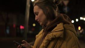 Το κοντό μαλλιαρό κορίτσι περπατά μέσω του χαμόγελου, των στάσεων και των πόλεων βραδιού στο smartphone Φορητό μήκος σε πόδηα απόθεμα βίντεο