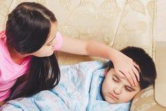 Το κορίτσι άγγιξε το μέτωπό του που ο άρρωστος αδελφός, ελέγχει τη θερμοκρασία Στοκ Φωτογραφίες