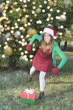 Το κορίτσι Άγιου Βασίλη κλωτσά τα χριστουγεννιάτικα δώρα στοκ εικόνα