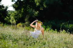 Το κορίτσι άσπρα sundress και ένα στεφάνι των λουλουδιών στο κεφάλι της κάθεται Στοκ φωτογραφία με δικαίωμα ελεύθερης χρήσης