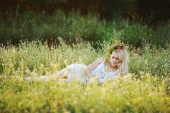 Το κορίτσι άσπρα sundress και ένα στεφάνι των λουλουδιών στο κεφάλι της κάθεται Στοκ εικόνα με δικαίωμα ελεύθερης χρήσης