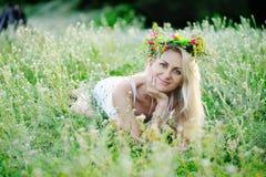 Το κορίτσι άσπρα sundress και ένα στεφάνι των λουλουδιών στο κεφάλι της κάθεται Στοκ εικόνες με δικαίωμα ελεύθερης χρήσης