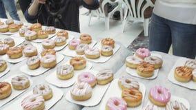 Το κορίτσι έβαλε ζωηρόχρωμα doughnuts στον εξυπηρετούμενο πίνακα από το κιβώτιο στο εμπορικό κέντρο δίκαιος απόθεμα βίντεο
