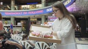 Το κορίτσι έβαλε ζωηρόχρωμα doughnuts στον εξυπηρετούμενο πίνακα στο εμπορικό κέντρο δίκαιος άνθρωποι φιλμ μικρού μήκους