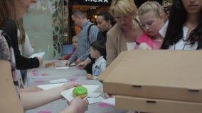 Το κορίτσι έβαλε ζωηρόχρωμα doughnuts στον πίνακα για τους ανθρώπους στο εμπορικό κέντρο δίκαιος αρτοποιών απόθεμα βίντεο
