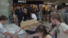 Το κορίτσι έβαλε ζωηρόχρωμα doughnuts στον πίνακα στο εμπορικό κέντρο δίκαιος Οι άνθρωποι παίρνουν το γλυκό φιλμ μικρού μήκους