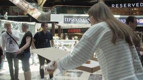 Το κορίτσι έβαλε ζωηρόχρωμα doughnuts στον πίνακα στο εμπορικό κέντρο δίκαιος πολλοί άνθρωποι φιλμ μικρού μήκους
