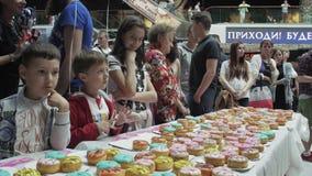 Το κορίτσι έβαλε ζωηρόχρωμα doughnuts στον πίνακα στο εμπορικό κέντρο δίκαιος Αναμονή παιδιών φιλμ μικρού μήκους
