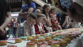 Το κορίτσι έβαλε ζωηρόχρωμα doughnuts στον πίνακα στο εμπορικό κέντρο δίκαιος Ευτυχή παιδιά φιλμ μικρού μήκους