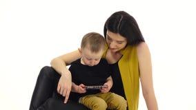 Το κορίτσι λέει και παρουσιάζει κάτι στο smartphone στο παιδί της Άσπρη ανασκόπηση απόθεμα βίντεο